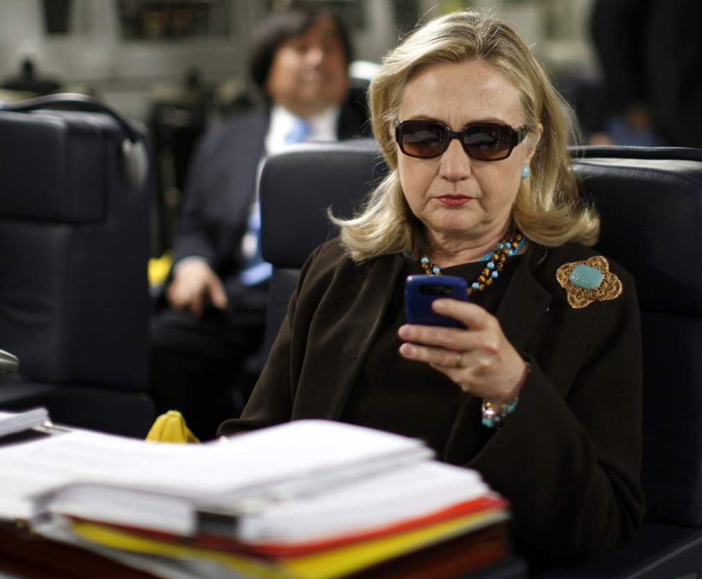 Former U.S. Secretary of State Hillary Clinton checks her PDA upon her departure in a military C-17 plane from Malta bound for Tripoli, Libya, in this October 18, 2011, file photo. An investigative committee in the U.S. House of Representatives will subpoena Clinton's personal emails regarding the 2012 attack on the U.S. consulate in Benghazi, Libya, the Washington Post reported on March 4, 2015.  REUTERS/Kevin Lamarque/Files  (LIBYA - Tags: POLITICS)
